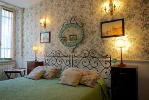 Sovrummen på det lilla hotellet Arco dei Tolemei domineras av antikviteter.