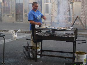 Fiskgrillen står mitt på gatan och bevakas inte bara av grillmästaren utan också av ett rejält band med måsar.