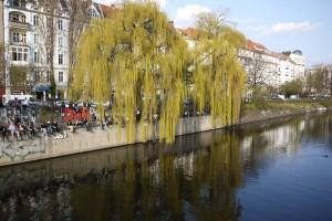 Kanterna av Landwehrkanal är fyllda av människor som gläds åt sommartemperaturerna.