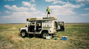 Ung man vaktar för hyenor i Serengeti.